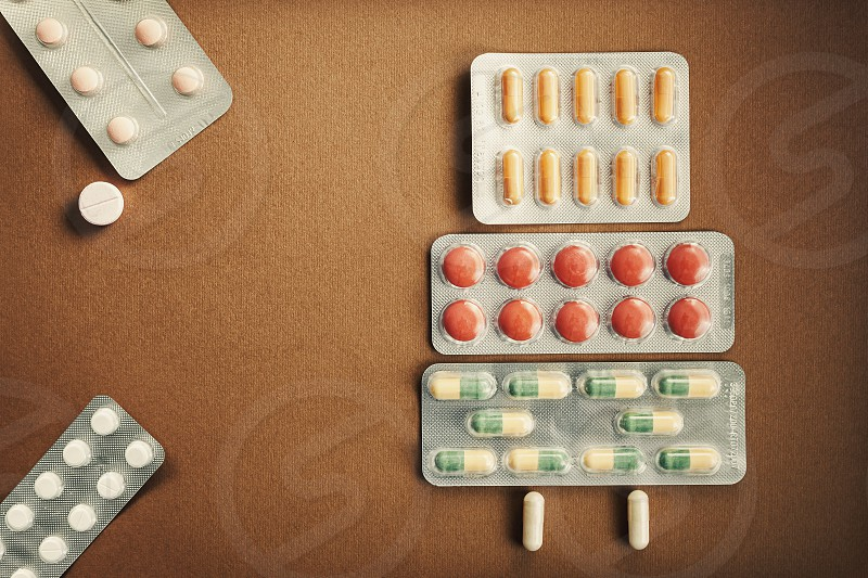 Various packs of pills and tablets colorful drugs all around the scene.  photo