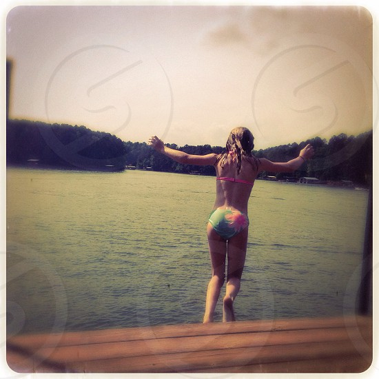 Girl jumping off dock photo