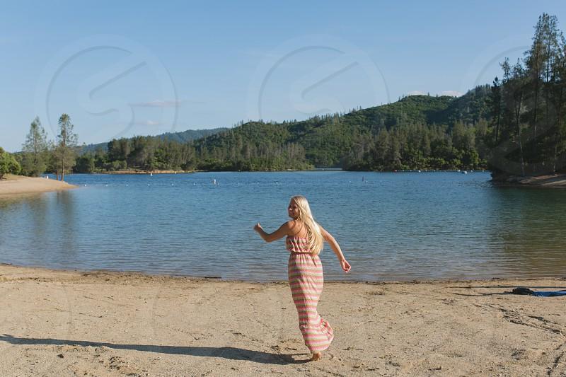 girl runs towards lake  photo