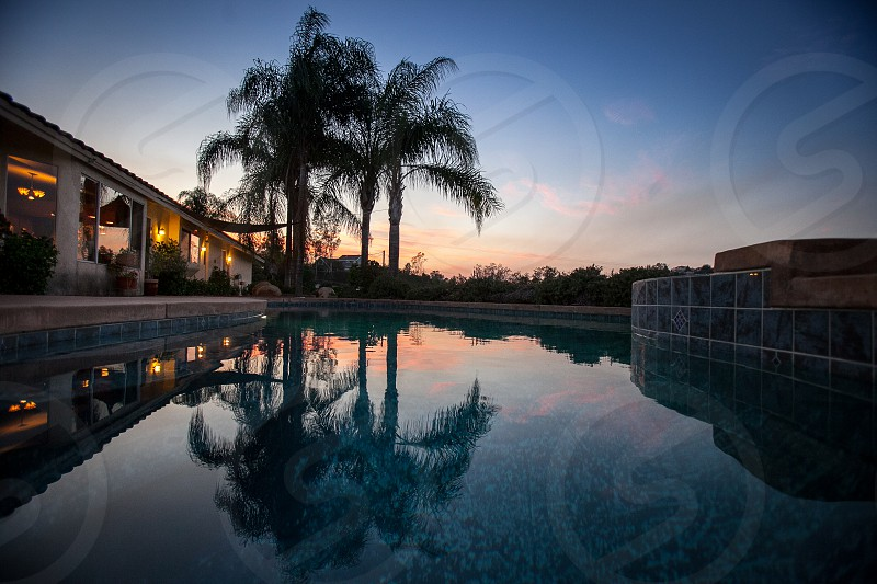 A luxurious family home in Southern California. House residence neighborhood suburban property pool sunset palm trees.  photo