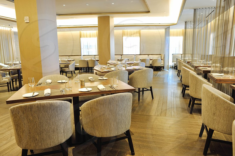 interior restaurant view with set tables and tan bucket chairs photo