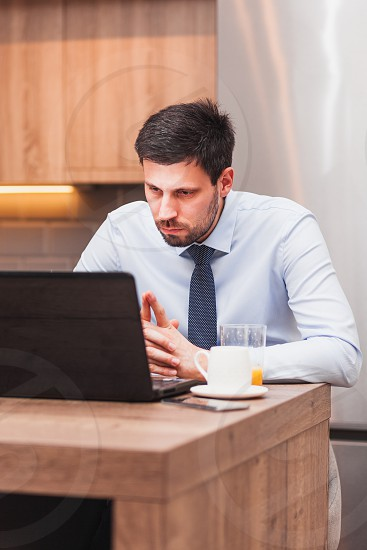 Young businessman working on laptop at home photo