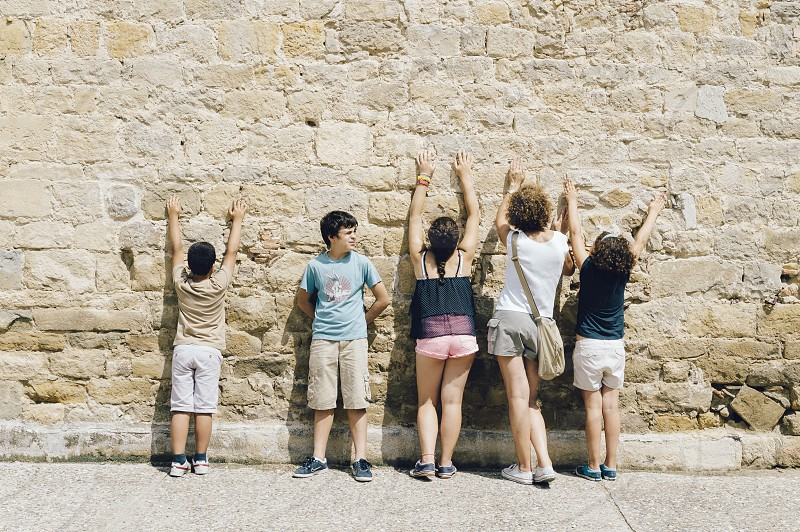 Family back with hands raised against a stone wall. One of them looks at the front photo