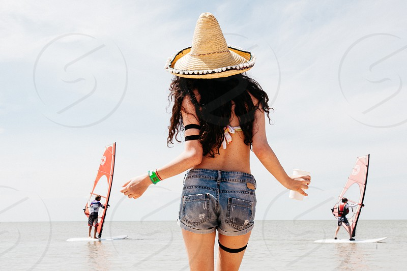 Girl standing at the beach looking at windsurfers photo