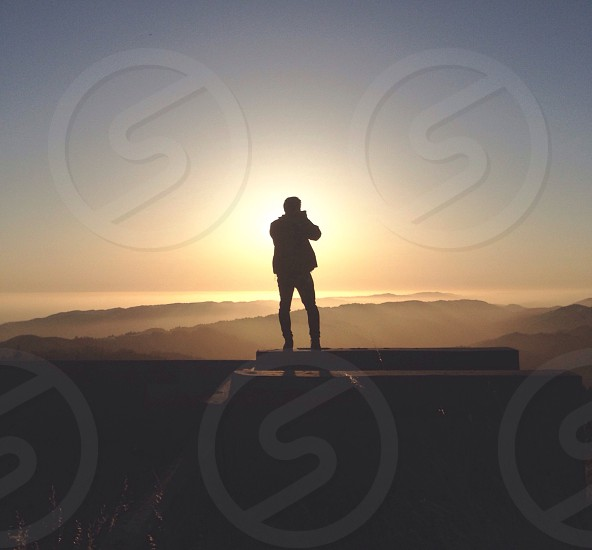 human standing on top of a mountain photo photo