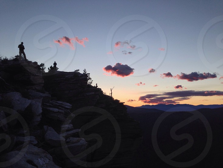 man on top of the mountain silhouette photo