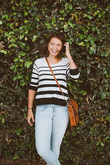 woman in white and black striped long sleeved top and blue denim jeans carrying brown leather messenger bag photo