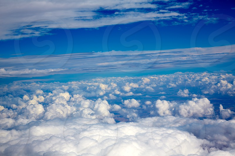 Aerial view of clouds and blue sky while flying on aircraft photo