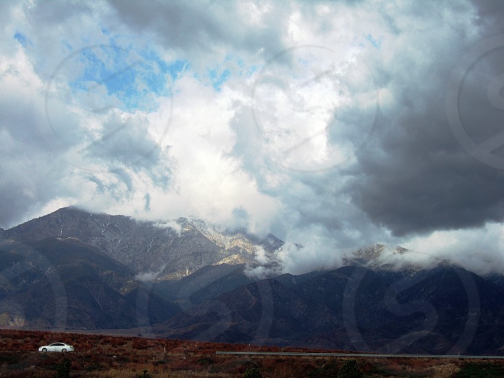 At a distace a white car drives done an empty highway near cloud covered hills. photo