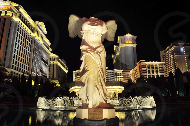 photo of no head womanwith wings statue with fountain on side surrounded whit concrete buildings during night time photo