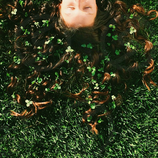 Shamrocks and Curls.  Young girl laying on grass with shamrocks in hair. photo