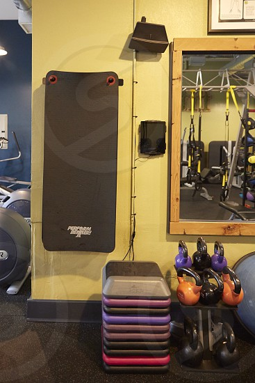 gym interior with wall mounted speakers mirror kettle bells and weight plates photo