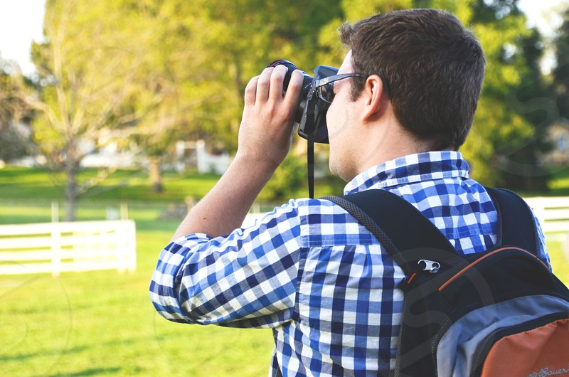 man holding camera capturing photo