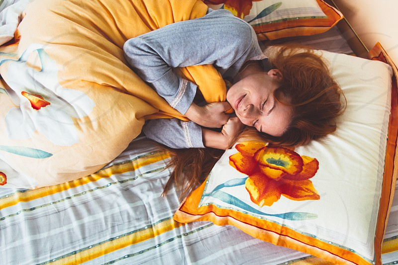 Young woman sleeping in bed with a smile on her face  photo