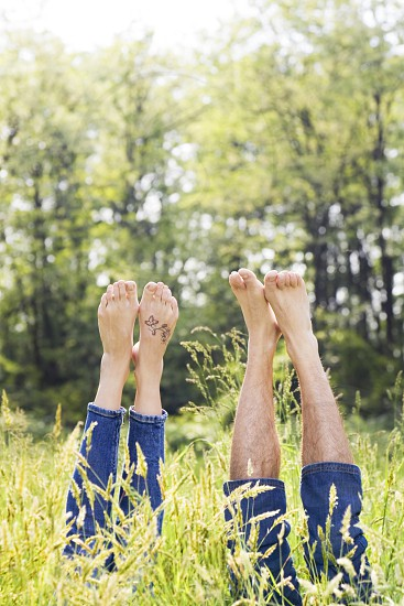 couple; jeans; human leg; fun; grass; love; Togetherness; lying down; barefoot; relaxation; park; happy; meadow; together; Happiness; copy space; girlfriend; boyfriend; young adult; playing; leisure; human feet; People; two; man; woman; field; country; romance; carefree; nature; outdoors; caucasian; day; Adults; green; stretching; leisure activity; 20-25 years; 25-30 years; 30-35 years; guy; cheerful; low section; summer; spring photo