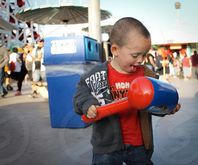 Boy enjoying his  souvenir at Santa Cruz beach Boardwalk.  photo