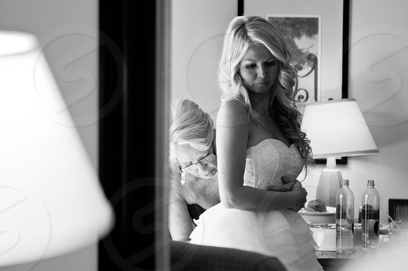 woman wearing bridal dress standing in front of mirror black and white photo photo