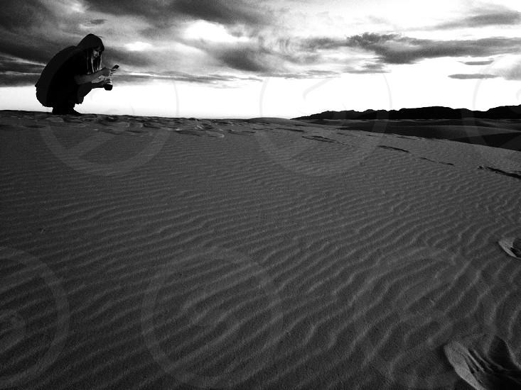 woman bending down on sandy photo