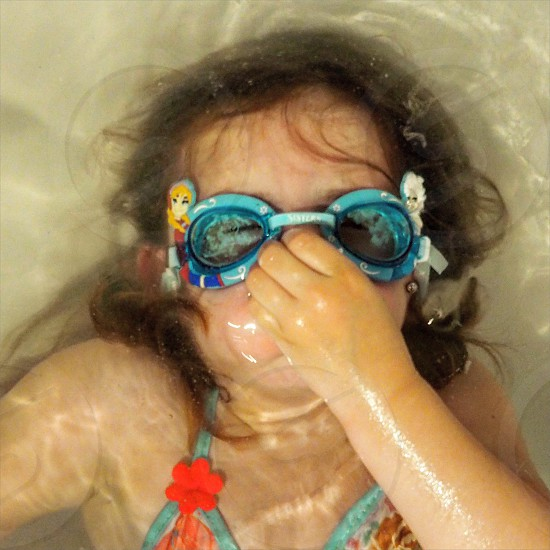 girl wearing a teal goggles covering her nose with left hand while holding breath under water photo