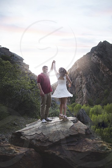 man with red shirt and woman with white dress on a rock photo