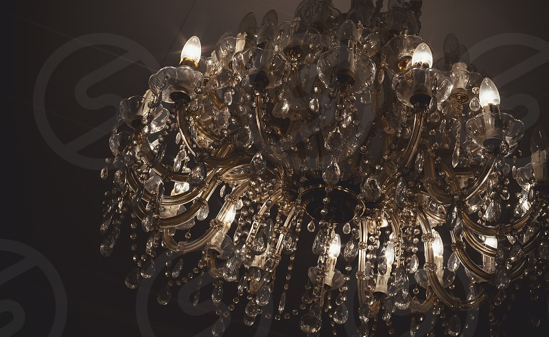 Chandelier details vintage style with lot of crystal parts and light bulbs.  photo