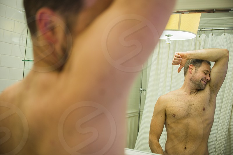topless man standing in front of mirror photo