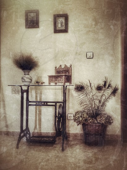 brown wooden trinket and white vase on black steel sewing table beside brown woven basket with flowers photo