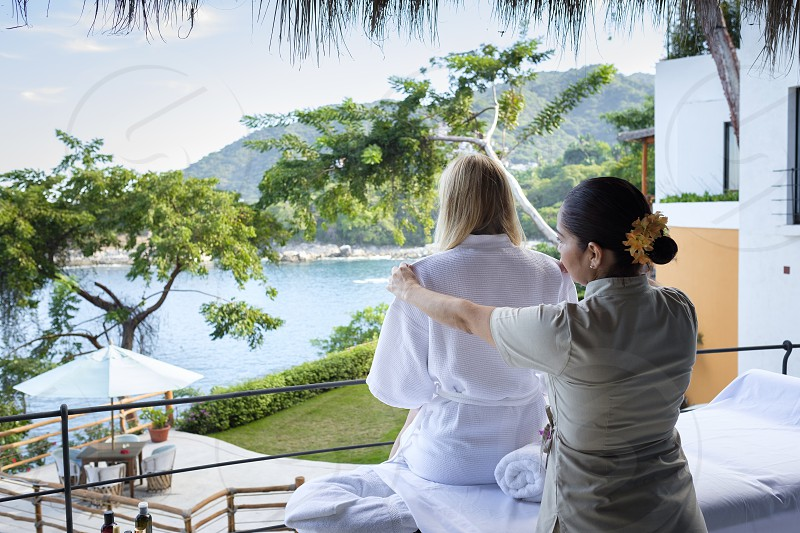 Massage therapist helping woman out of her bathrobe to get ready for her outdoor massage at luxury ocean front villa in Mexico. photo