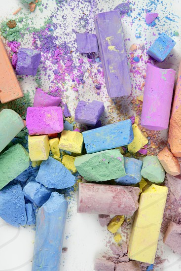 Colorful chalk broken colors mess over white background photo