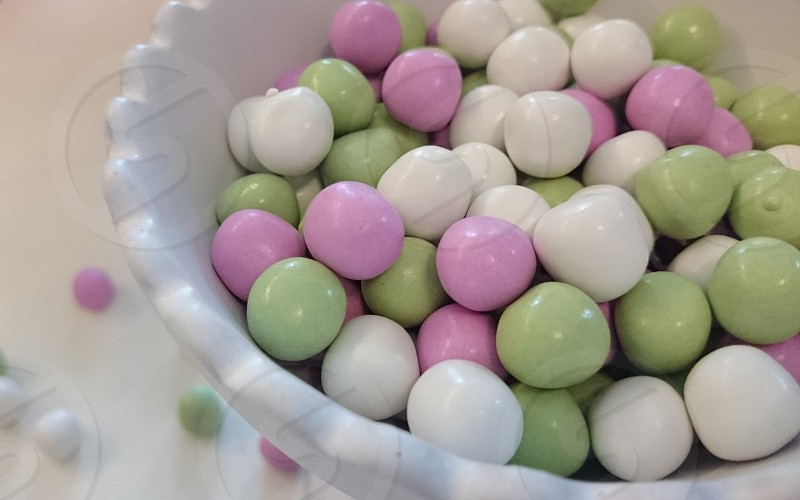 white purple and green candy coated gums in the bowl photo