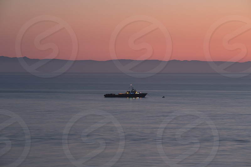 Commercial boat out in the ocean during sunset. Long exposure photo