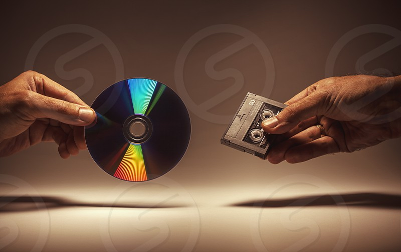 Conceptual composition two male hands hold a digital audio tape and a CD.  photo