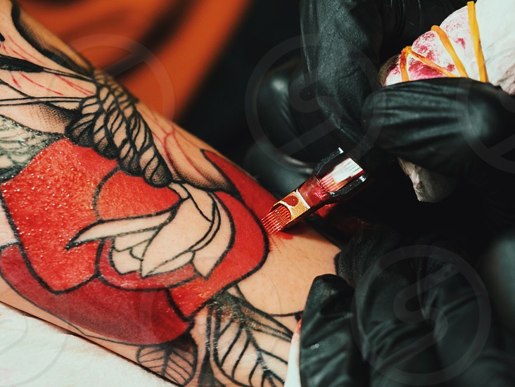 Tattoo artist at work. Woman in black latex glove tattooing a young man's hand with colorful picture in studio. Close up. photo