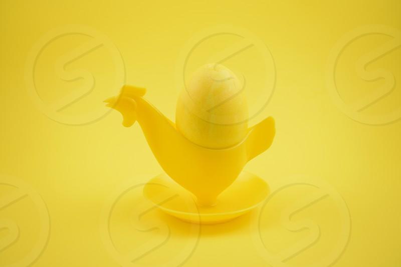 Yellow egg. Chicken egg holder. Easter egg on a yellow background. Plastic egg cup on a yellow background. Breakfast still life. Easter concept photo