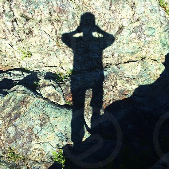 man shadow on rock photo