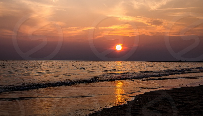 calm sea wave at sea shore under cloudy sky at sunset photo