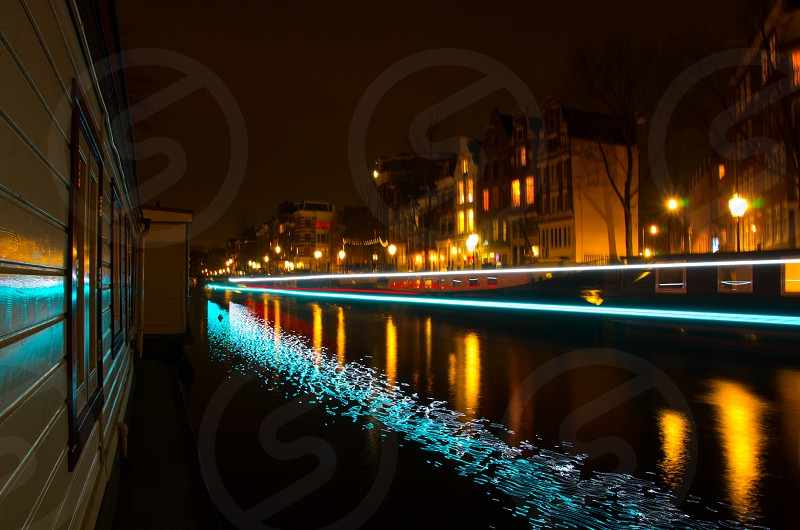 View from an Amsterdam houseboat with light trails from a tourboat that passed by photo