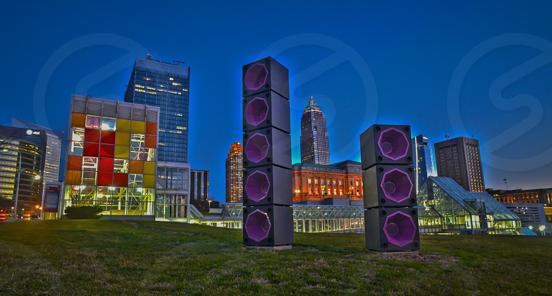 Speakers from the Rock and Roll Hall of Fame set in front of the Cleveland skyline just after sunset photo