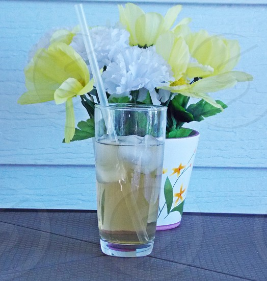 beverage glass infront of yellow flower in white ceramic vase photo