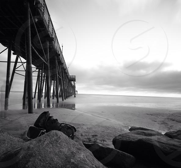 grayscale photo of bag on rock under wooden bridge photo