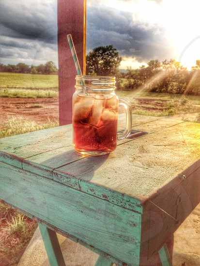 clear glass mug with brown liquid inside photo