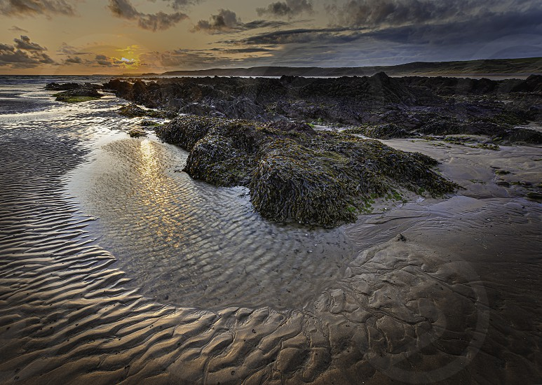 Ethereal sunset scene on scenic rocky beach in Freshwater West on Pembrokeshire coastSouth Wales UK. Reflection of sun in puddle of sea water rippled sand and rocks covered by seaweed. photo