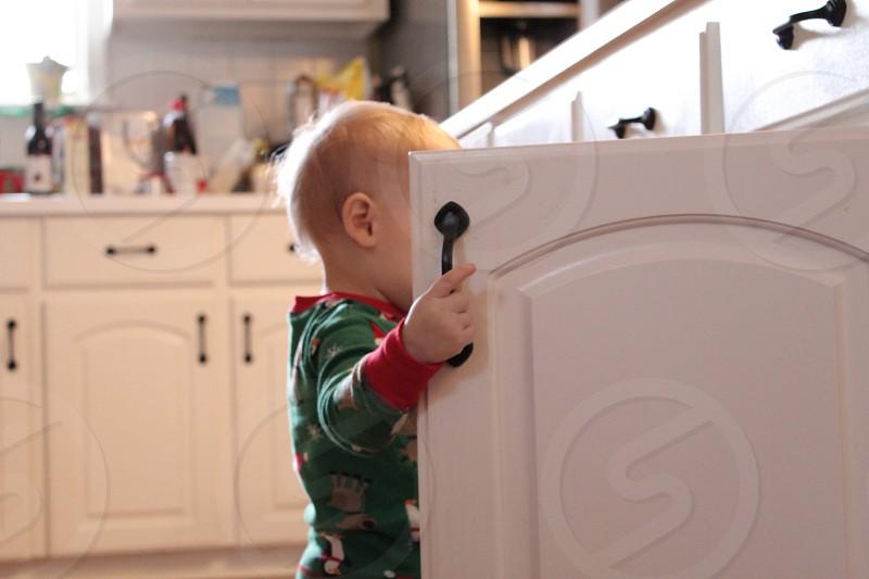 toddler standing near open kitchen cabinet photo