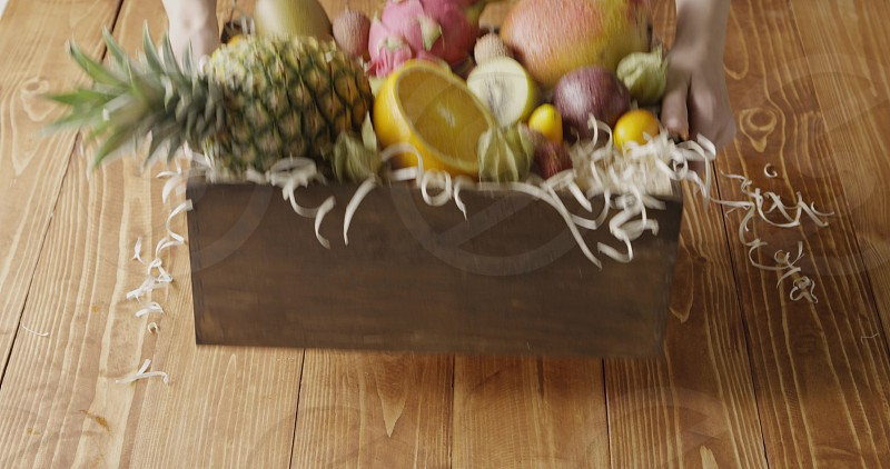 Box with assortment of freshly picked natural exotic fruits -ananas passion fruit mango on a wood shaving. Girl's hand put container on a wooden background. Motion 4K UHD video 3840 2160p. photo