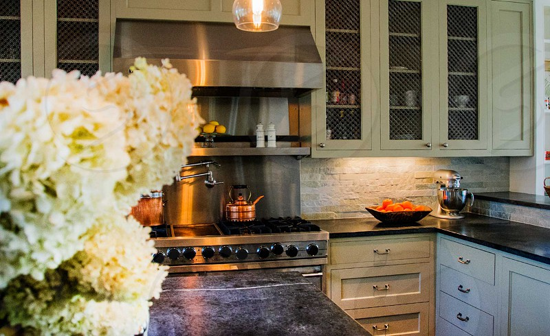 white cluster flowers beside stainless steel kettle under stainless steel kitchen hood photo