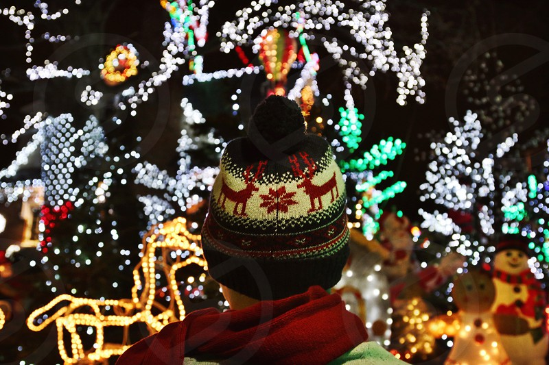 person wearing brown white and red reindeer knit cap infront of christmas lights photo