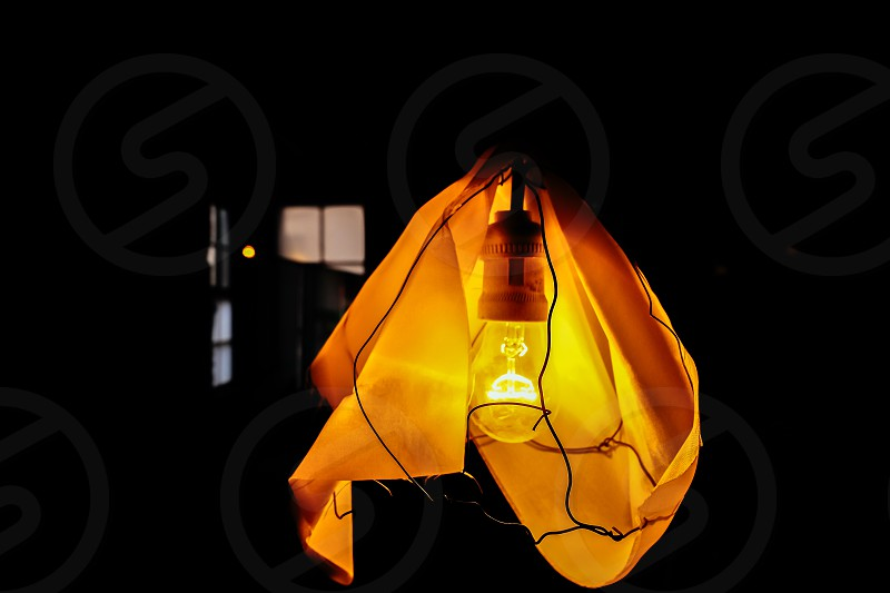 Old-fashioned hanging lightbulb covered with cloth photo