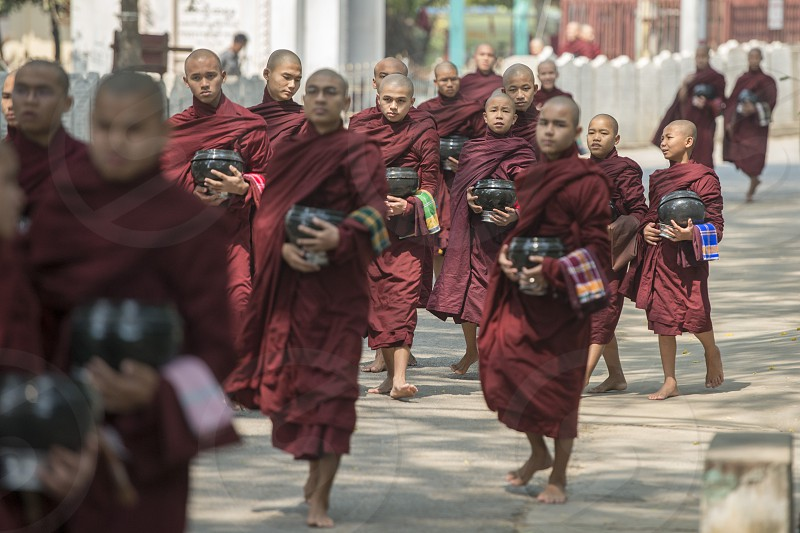 monks are on the way to the lunch at the Mahagandayon Monastery in Amarapura near the City of Mandalay in Myanmar in Southeastasia. photo