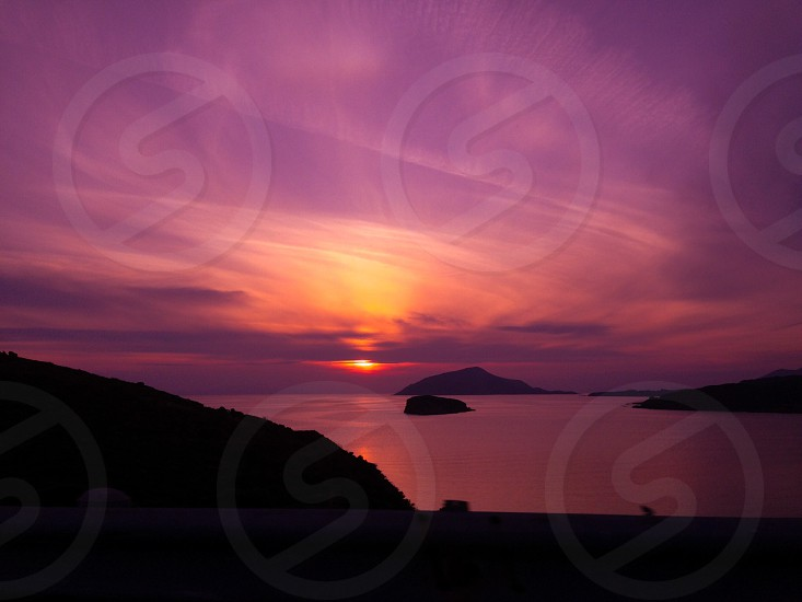 pink sunset above mountain and ocean  water photo
