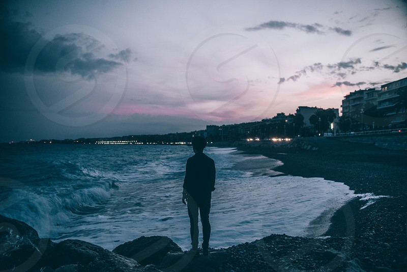 person standing on rock by the beach shore with sea waves crashing during dusk photo